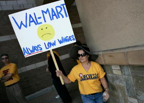 Diana Huffman holds a sign in support of striking Walmart workers protesting unsafe working conditions and poor wages in Pico Rivera